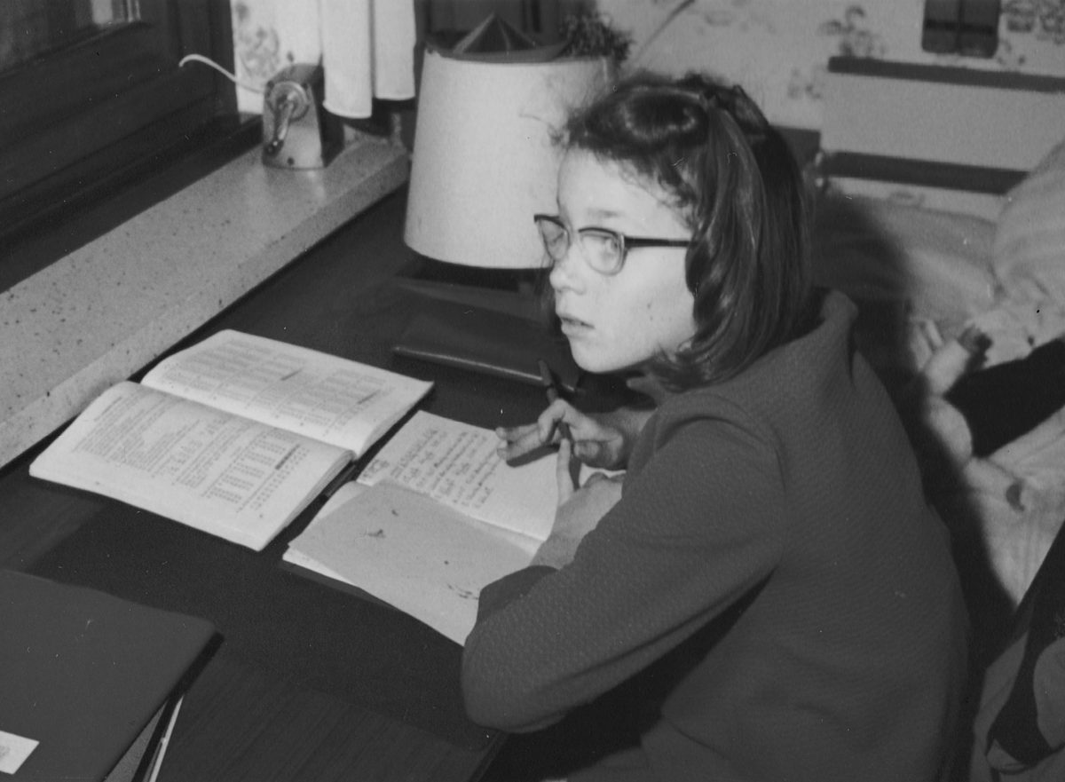 9-year-old Claudia doing school homework wearing her glasses